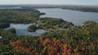 AX148_230 - 6K stock footage aerial video flying over fall foliage toward a pond and coastal town, Bar Harbor, Maine