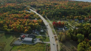 AX148_233 - 6K stock footage aerial video flying over road through forest with colorful fall foliage, Bar Harbor, Maine
