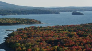 AX149_002 - 6K stock footage aerial video flying away from the bay and over forest with fall foliage, Trenton, Maine