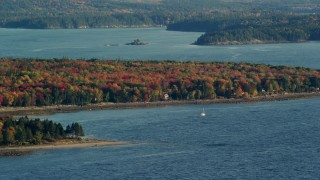 AX149_007 - 6K stock footage aerial video flying by forest with colorful fall foliage along a cove, Trenton, Maine