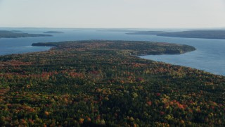 AX149_009 - 6K stock footage aerial video flying high above forest with colorful fall foliage along water, Surry, Maine