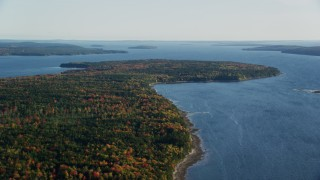 AX149_010 - 6K stock footage aerial video flying over forest with fall foliage toward the water, autumn, Surry, Maine