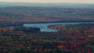 AX149_011 - 6K stock footage aerial video flying by a lake surrounded by a forest with fall foliage, Surry, Maine