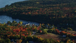 AX149_012 - 6K stock footage aerial video flying by a coastal town toward the water surrounded by autumn trees, Blue Hill, Maine