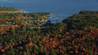 AX149_014 - 6K stock footage aerial video flying over autumn forest away from a coastal neighborhood, Blue Hill, Maine