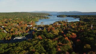AX149_019 - 6K stock footage aerial video flying by coastal town and harbor among fall foliage, Blue Hill, Maine