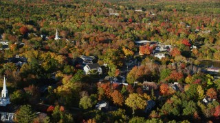 AX149_021 - 6K stock footage aerial video flying along a small town with church steeples, nestled among fall foliage, Blue Hill, Maine