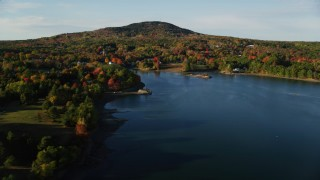 AX149_022 - 6K stock footage aerial video flying away from coastal town among fall foliage and harbor, Blue Hill, Maine