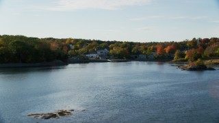 AX149_026 - 6K stock footage aerial video flying over water toward coastal town and fall foliage, Blue Hill, Maine