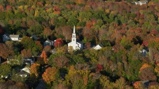 AX149_029 - 6K stock footage aerial video flying away from a small town and white church among fall foliage, Blue Hill, Maine