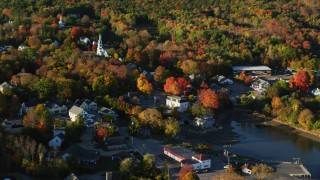 AX149_031 - 6K stock footage aerial video passing by a small coastal town and fall foliage, Blue Hill, Maine