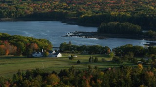 AX149_064 - 6K stock footage aerial video flying by an isolated home, colorful foliage in autumn, Penobscot, Maine