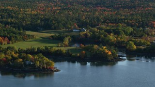 AX149_066 - 6K stock footage aerial video flying by rural waterfront homes, colorful forest, autumn, Penobscot, Maine