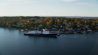 AX149_070 - 6K stock footage aerial video orbiting small coastal town, State of Maine training ship, autumn, Castine, Maine
