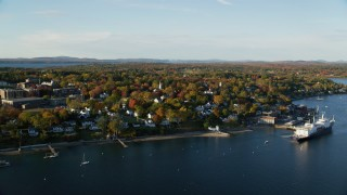 AX149_071 - 6K stock footage aerial video orbiting a coastal town, State of Maine training ship, among fall foliage, autumn, Castine, Maine