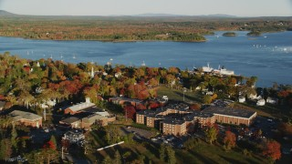 AX149_074 - 6K stock footage aerial video orbiting Maine Maritime Academy nestled among fall foliage, autumn, Castine, Maine