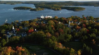 AX149_076 - 6K stock footage aerial video orbiting a small coastal town and training ship, autumn, Castine, Maine