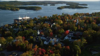 AX149_077 - 6K stock footage aerial video orbiting away from a small coastal town with fall foliage, autumn, Castine, Maine