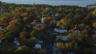 AX149_079 - 6K stock footage aerial video orbiting small town homes and white church in autumn, Castine, Maine