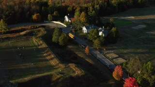 AX149_082 - 6K stock footage aerial video approaching and flying by houses, school bus in a small town, autumn, Castine, Maine