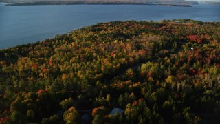 AX149_084 - 6K stock footage aerial video flying over colorful forest, rural road and homes, autumn, Castine, Maine