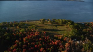 AX149_085 - 6K stock footage aerial video flying over colorful forest, approach rural waterfront homes, autumn, Castine, Maine