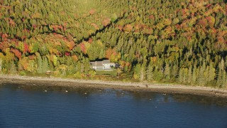 AX149_086 - 6K stock footage aerial video flying by isolated waterfront home, colorful forest, autumn, Castine, Maine