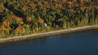 AX149_087 - 6K stock footage aerial video flying by rural waterfront home, colorful forest, autumn, Castine, Maine