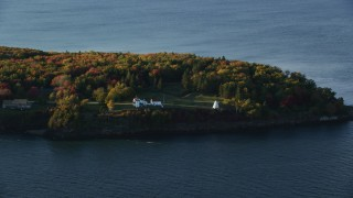 AX149_088 - 6K stock footage aerial video flying by Fort Point Light, among fall foliage, autumn, Stockton Springs, Maine