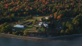 AX149_090 - 6K stock footage aerial video flying by French's Point in front of colorful forest, autumn, Stockton Springs, Maine