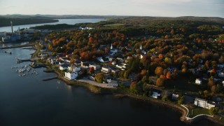 AX149_104 - 6K stock footage aerial video orbiting small coastal town, colorful trees, autumn, Bucksport, Maine