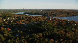 AX149_108 - 6K stock footage aerial video flying over trees by a small town on Penobscot River, autumn, Bucksport, Maine