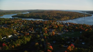 AX149_109 - 6K stock footage aerial video flying by a small town on the Penobscot River in autumn, Bucksport, Maine