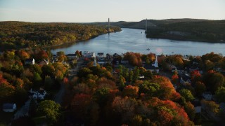 AX149_112 - 6K stock footage aerial video flying over small town, approaching a bridge, autumn, Bucksport, Maine