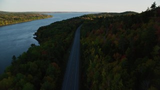 AX149_117 - 6K stock footage aerial video flying over Route 3, colorful forest in autumn, Stockton Springs, Maine, sunset