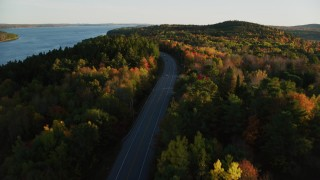 AX149_118 - 6K stock footage aerial video flying over a road among colorful forest in autumn, Stockton Springs, Maine, sunset