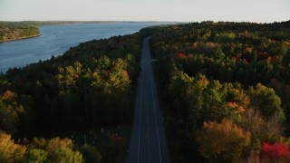 AX149_120 - 6K stock footage aerial video flying over quiet road among a colorful forest in autumn, Stockton Springs, Maine, sunset