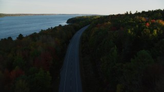 AX149_121 - 6K stock footage aerial video flying over road with no traffic, colorful forest in autumn, Stockton Springs, Maine, sunset