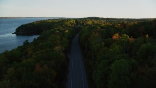 AX149_122 - 6K stock footage aerial video flying over a road situated among, colorful forest in autumn, Stockton Springs, Maine, sunset