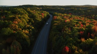 AX149_124 - 6K stock footage aerial video flying over forest road with light traffic, fall foliage, in autumn, Stockton Springs, Maine, sunset