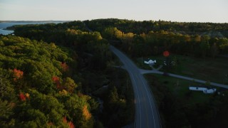 AX149_125 - 6K stock footage aerial video flying high over quiet road among colorful forest, autumn, Stockton Springs, Maine, sunset