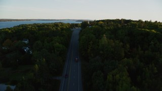 AX149_126 - 6K stock footage aerial video flying over road, approach church, cemetery, autumn, Stockton Springs, Maine, sunset