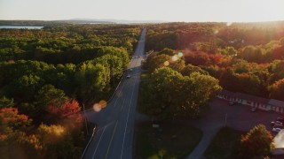 AX149_128 - 6K stock footage aerial video flying over road, colorful trees in autumn, Stockton Springs, Maine, sunset