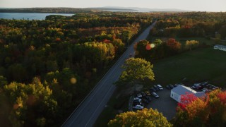 AX149_130 - 6K stock footage aerial video tracking car on road through forest in autumn, Stockton Springs, Maine, sunset