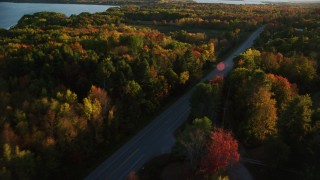 AX149_131 - 6K stock footage aerial video tracking car on road through forest, autumn, Stockton Springs, Maine, sunset