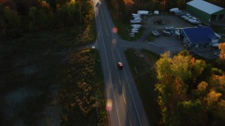 AX149_134 - 6K stock footage aerial video tracking car on road through forest in autumn, Stockton Springs, Maine, sunset