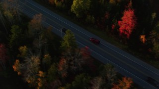 AX149_135 - 6K stock footage aerial video tracking car on road through forest in autumn, Stockton Springs, Maine, sunset