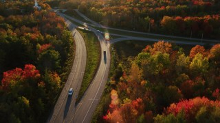 AX149_136 - 6K stock footage aerial video of a car on road approaching a church, autumn, Stockton Springs, Maine, sunset