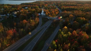 AX149_137 - 6K stock footage aerial video tracking car on road by near a white church, autumn, Stockton Springs, Maine, sunset