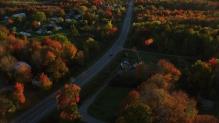 AX149_138 - 6K stock footage aerial video tracking car on road through small town, autumn, Stockton Springs, Maine, sunset